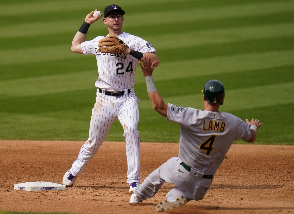 Oakland Athletics' Jake Lamb (4) is forced out at second by Colorado Rockies second baseman Ryan McMahon (24) during the sixth inning of a baseball ga...