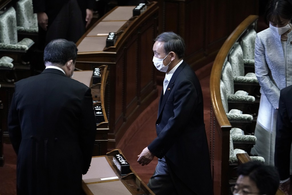Japan's new Prime Minister Yoshihide Suga, right, leaving after an extraordinary session at the upper house of parliament Thursday, Sept. 17, 2020, in...