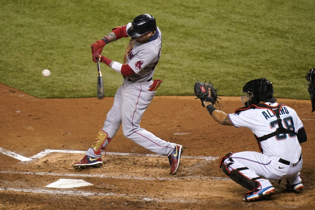 Boston Red Sox's Alex Verdugo, left, hits a single during the third inning of a baseball game against the Miami Marlins, Wednesday, Sept. 16, 2020, in...