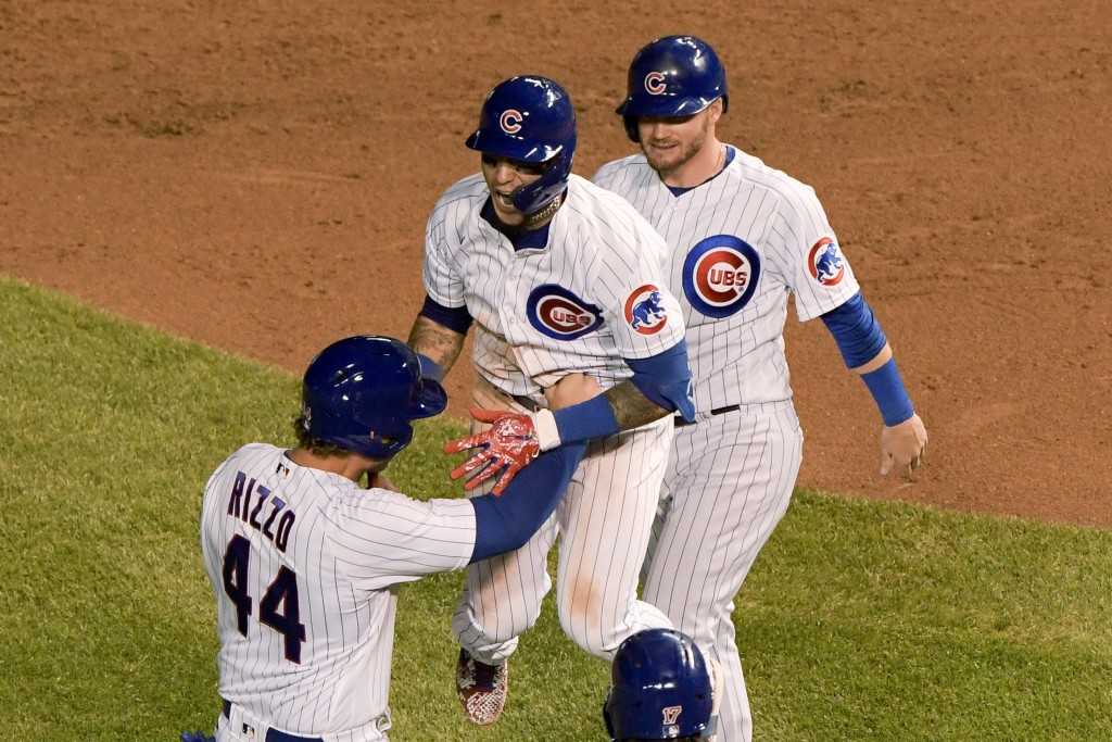 Chicago Cubs' Javier Baez, middle, celebrates with Anthony Rizzo (44) and Ian Happ (8) after driving in the winning run during the 10th inning against...