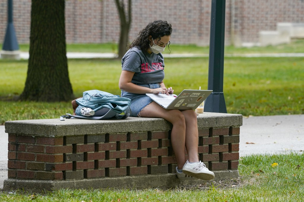 A masked student works on her laptop on the campus of Ball State University in Muncie, Ind., Thursday, Sept. 10, 2020. College towns across the U.S. h...