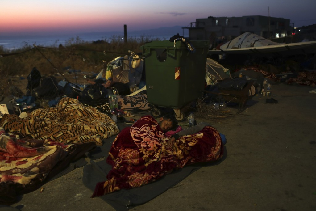 Migrants sleep next to a trash bin as they remained camped out on a road leading from Moria to the capital of Mytilene, on the northeastern island of ...