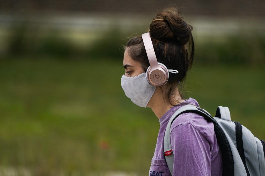 A masked student walks through the campus of Ball State University in Muncie, Ind., Thursday, Sept. 10, 2020. College towns across the U.S. have emerg...