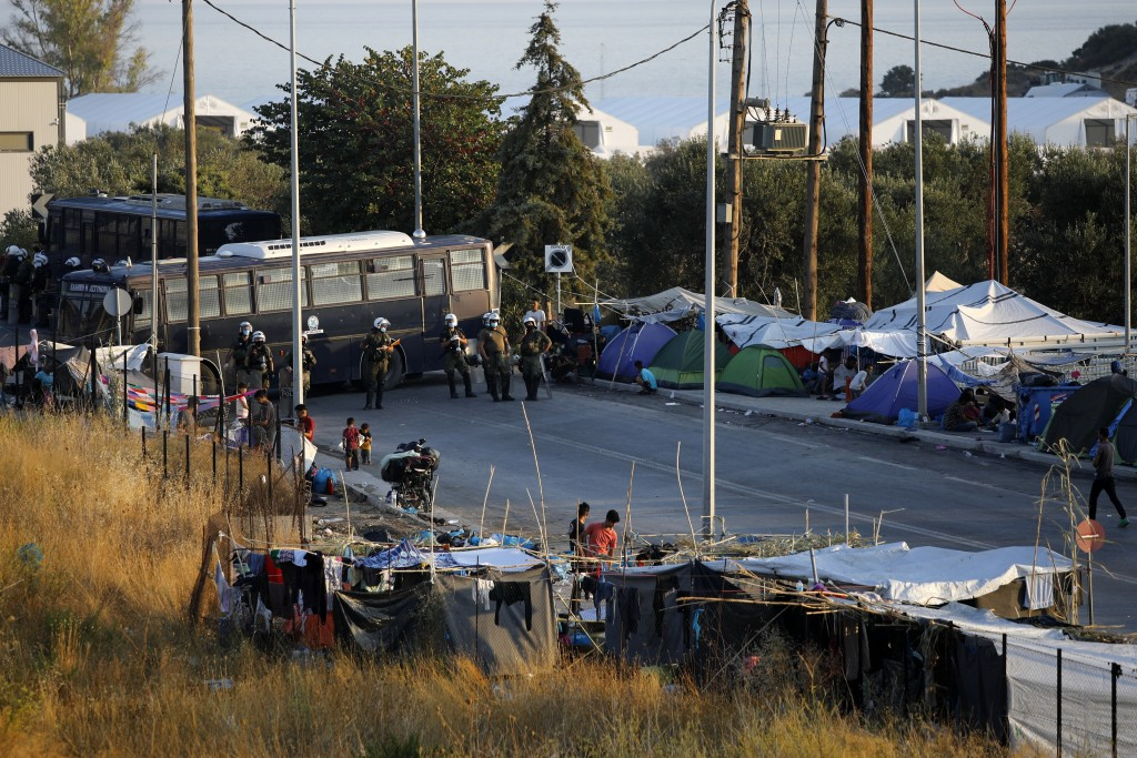 Riot police with buses block the access during an operation to evacuate a road leading from Moria to the capital of Mytilene, where migrants remained ...