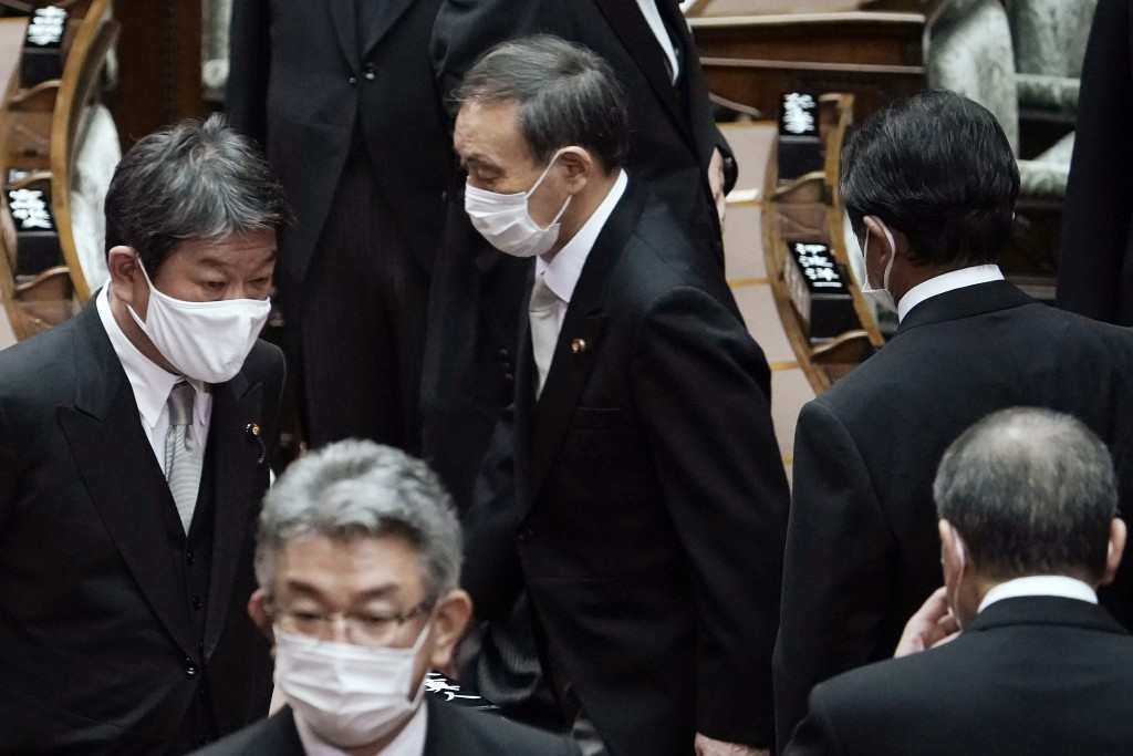 Japan's new Prime Minister Yoshihide Suga, center, walks out after attending an extraordinary session at the upper house of parliament Thursday, Sept....