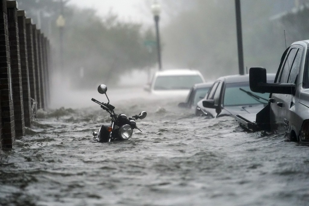 Cars and a motorcycle are underwater as water floods a street, Wednesday, Sept. 16, 2020, in Pensacola, Fla. Hurricane Sally made landfall Wednesday n...