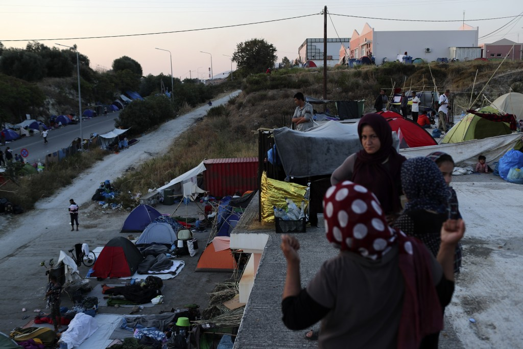 Migrants stand on a rooftop of a building as others remained camped out on a road leading from Moria to the capital of Mytilene, on the northeastern i...