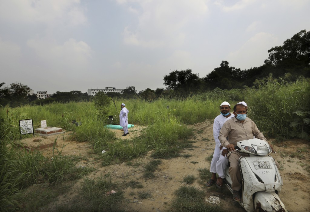 An Indian Muslim man looks for the grave of his relative who died of coronavirus in New Delhi, India, Wednesday, Sept. 16, 2020. India is now second i...