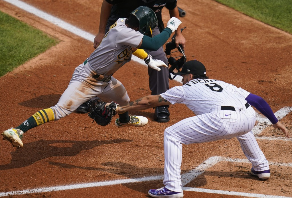 Oakland Athletics' Tony Kemp (5) avoids the tag at home plate by Colorado Rockies third baseman Josh Fuentes (8) during the third inning of a baseball...