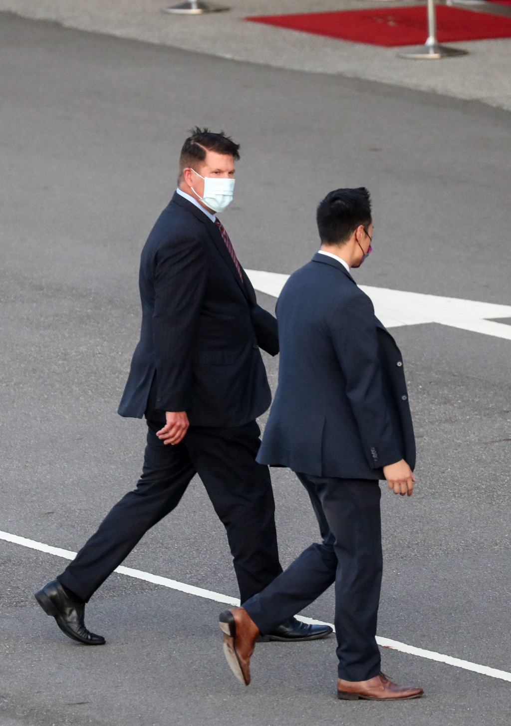 U.S. Under Secretary of State Keith Krach, left, walks away after disembarking from a plane upon arrival at the air force base airport in Taipei, Taiw...