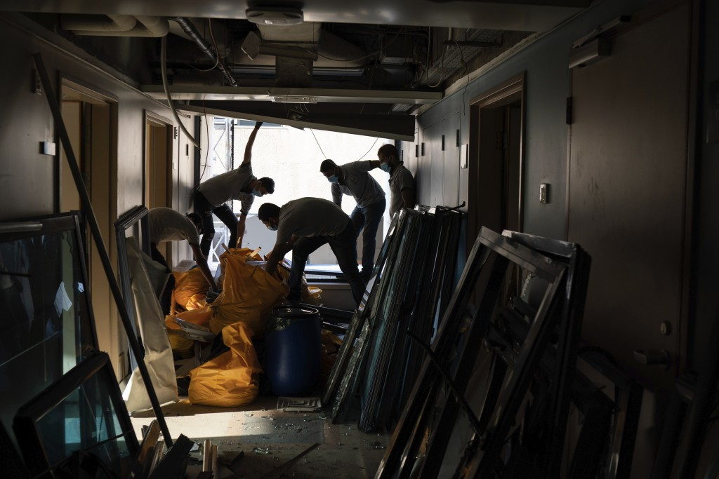 FILE - In this August 13, 2020 file photo, workers remove debris from the Saint George Hospital, that was heavily damaged in the Aug. 4 massive explos...