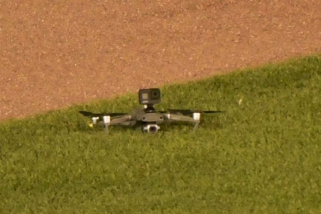 A drone lies on the grass after it landed in center field, before taking off again and flying out of the stadium, during the fifth inning of a basebal...
