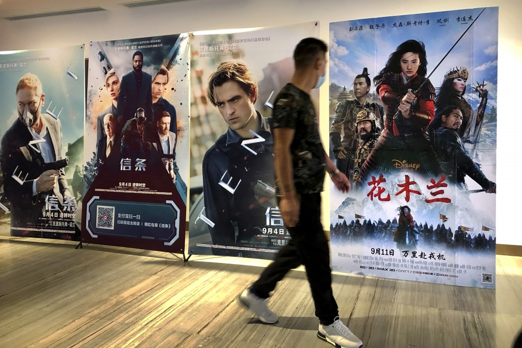 """A man wearing a face mask walks past a poster for the Disney movie """"Mulan"""" at a movie theater in Beijing, on Sept. 11, 2020. The remake of """"Mulan"""" str..."""