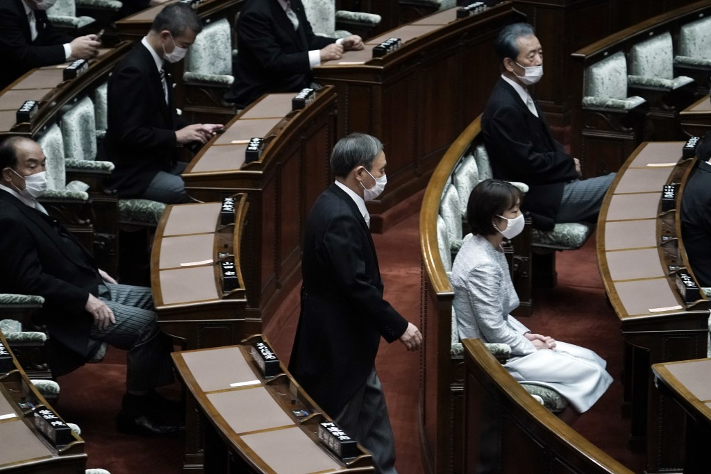 Japan's new Prime Minister Yoshihide Suga walks in to attend an extraordinary session at the upper house of parliament Thursday, Sept. 17, 2020, in To...