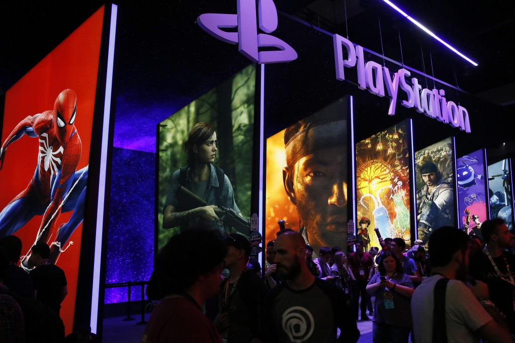 FILE - In this June 14, 2018, file people stand online next to the PlayStation booth at the 24th Electronic Entertainment Expo E3 at the Los Angeles C...