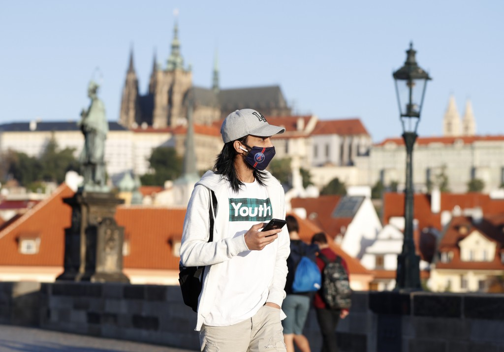 A young man wearing a face mask walks across the medieval Charles Bridge in Prague, Czech Republic, Friday, Sept. 18, 2020. The Czech Republic has bee...