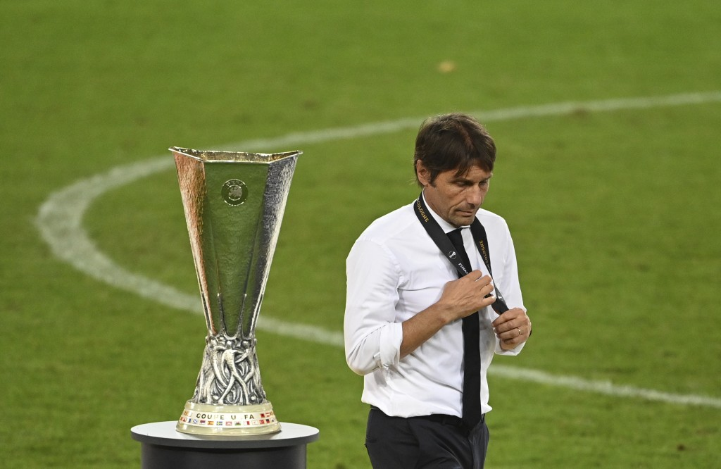 FILE - In this Aug. 21, 2020 file photo, Inter Milan's head coach Antonio Conte walks past the trophy after the Europa League final soccer match betwe...