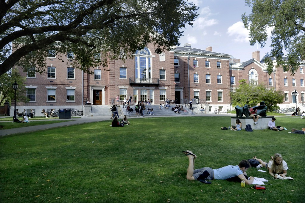 FILE - In this Sept. 25, 2019, file photo, people rest on grass while reading at Brown University in Providence, R.I. The university and attorneys for...