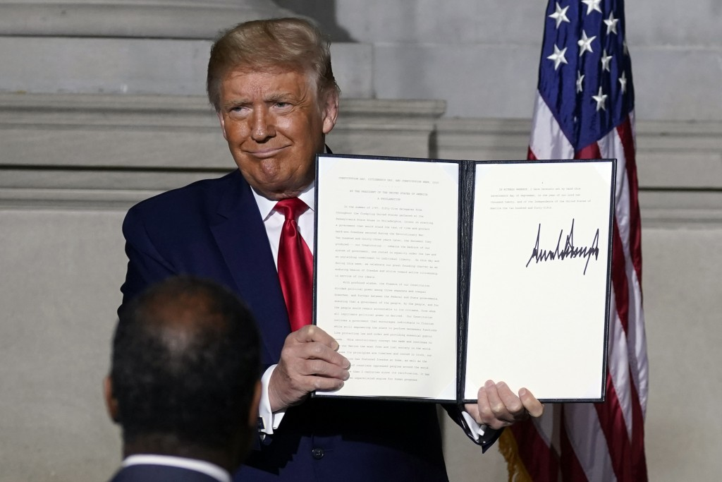 President Donald Trump holds a signed Constitution Day proclamation after he spoke to the White House conference on American History at the National A...