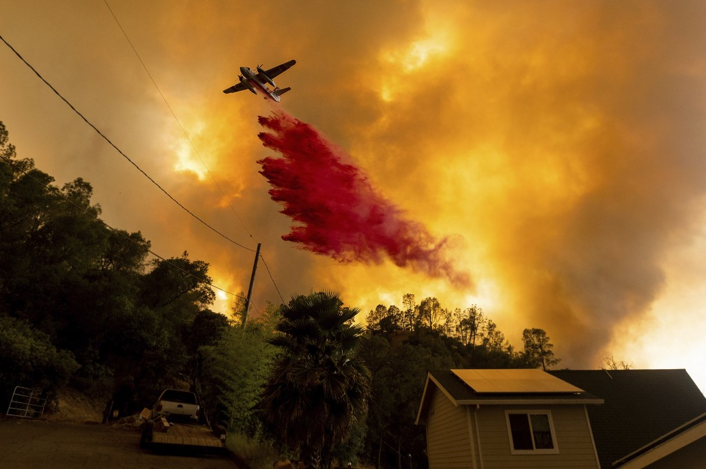 FILE - In this Aug. 18, 2020, file photo, an air tanker drops retardant as the LNU Lightning Complex fires tear through the Spanish Flat community in ...