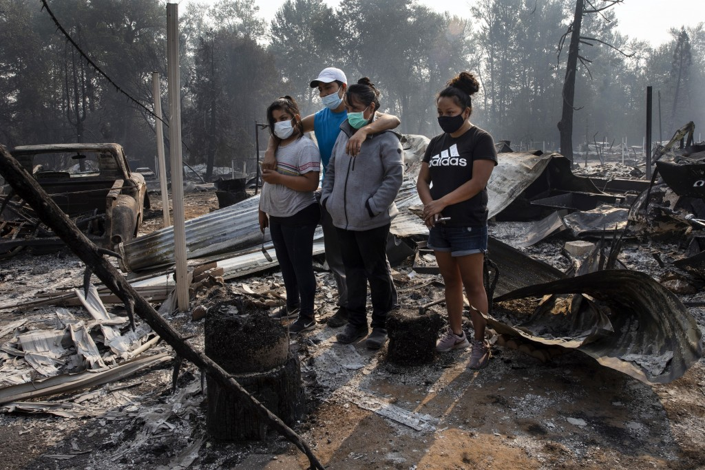 FILE - In this Sept. 10, 2020, file photo, The Reyes family looks at the destruction of their home at Coleman Creek Estates mobile home park in Phoeni...