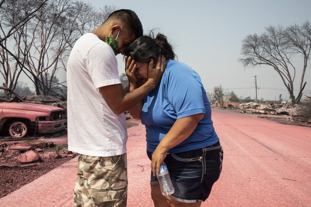 FILE - In this Sept. 10, 2020, file photo, Dora Negrete is consoled by her son Hector Rocha after seeing their destroyed mobile home at the Talent Mob...