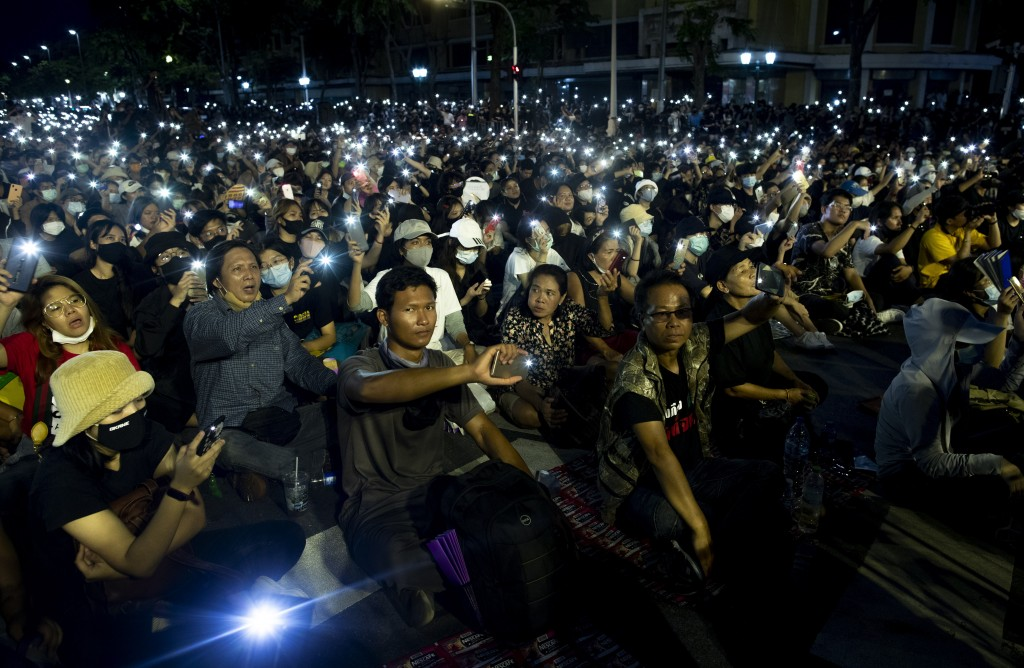 Pro-democracy activities display mobile phones with flash lights on during a protest at Democracy Monument in Bangkok, Thailand, Sunday, Aug, 16, 2020...