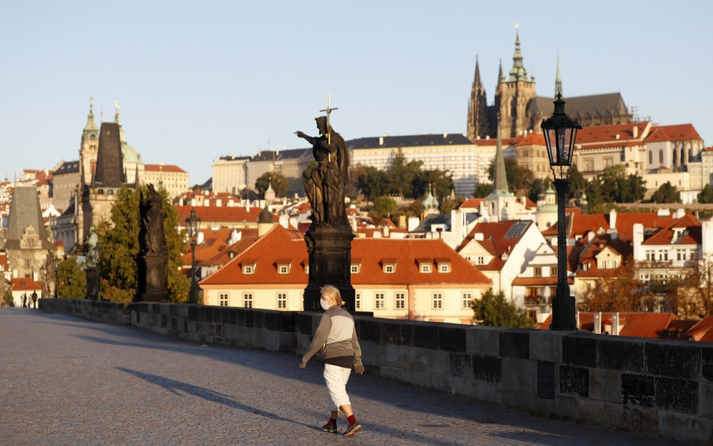 A woman wearing a face mask walks across the medieval Charles Bridge in Prague, Czech Republic, Friday, Sept. 18, 2020. The Czech Republic has been be...