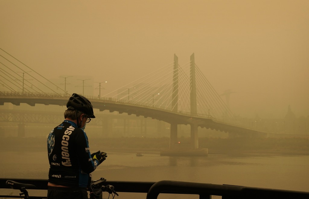 FILE - In this Sept. 12, 2020, file photo, a man stops on his bike along the Willamette River as smoke from wildfires partially obscures the Tilikum C...