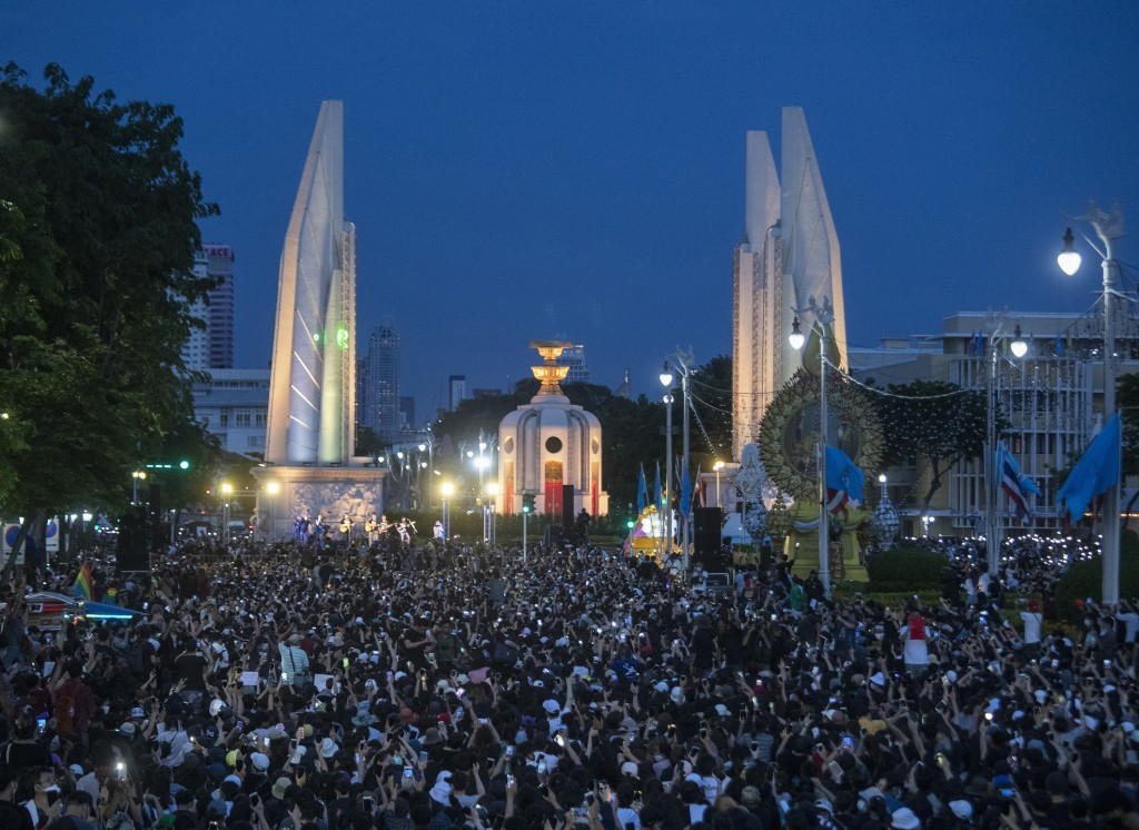 Pro-democracy students hold mobile phones with flashlights switched on in front of Democracy Monument during a rally in Bangkok, Thailand, Sunday, Aug...