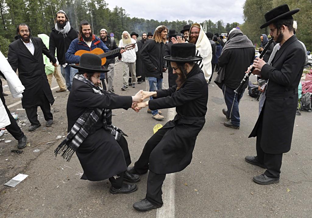 Hasidic Jewish pilgrims dance as they gather in front of Ukrainian border guards at the checkpoint Novaya Guta near Novaya Guta, Belarus, Friday, Sept...
