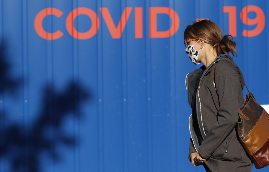 A woman wearing a face mask walks to get tested for COVID-19 at a sampling station in Prague, Czech Republic, Friday, Sept. 18, 2020. The Czech Republ...