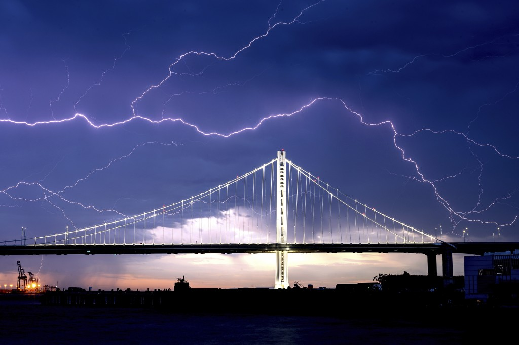 FILE - In this Aug. 16, 2020, file photo, lightning forks over the San Francisco-Oakland Bay Bridge as a storm passes over Oakland, Calif. Numerous li...