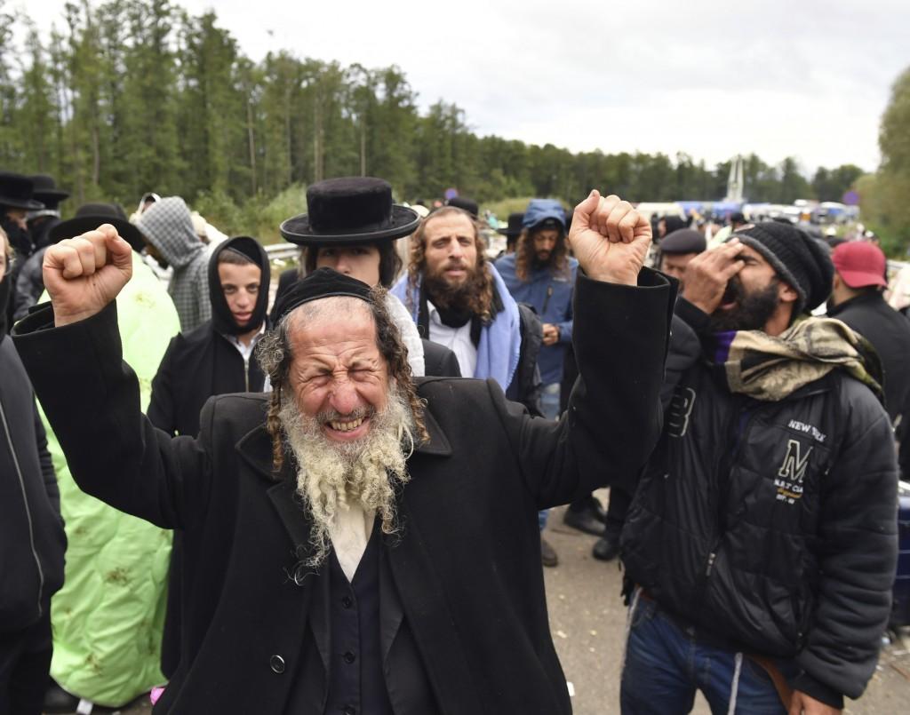 A Hasidic Jewish pilgrim reacts as he joins others, in front of Ukrainian border guards at the checkpoint Novaya Guta near Novaya Guta, Belarus, Frida...