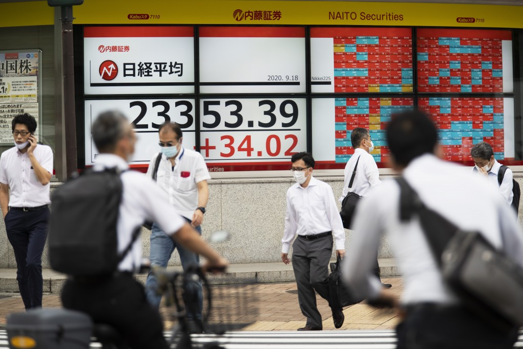 Men walk by screens showing Japan's Nikkei 225 index at a securities firm in Tokyo on Friday, Sept. 18, 2020. Asian shares were slightly higher Friday...