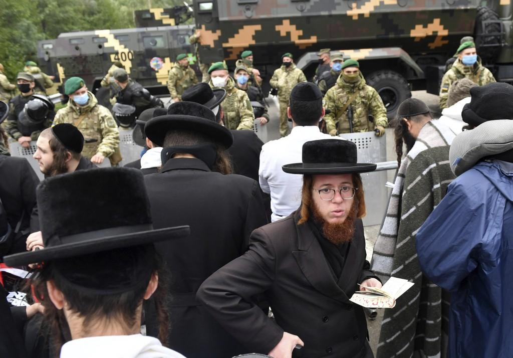 Hasidic Jewish pilgrims gather in front of Ukrainian border guards at the checkpoint Novaya Guta near Novaya Guta, Belarus, Friday, Sept. 18, 2020. Uk...