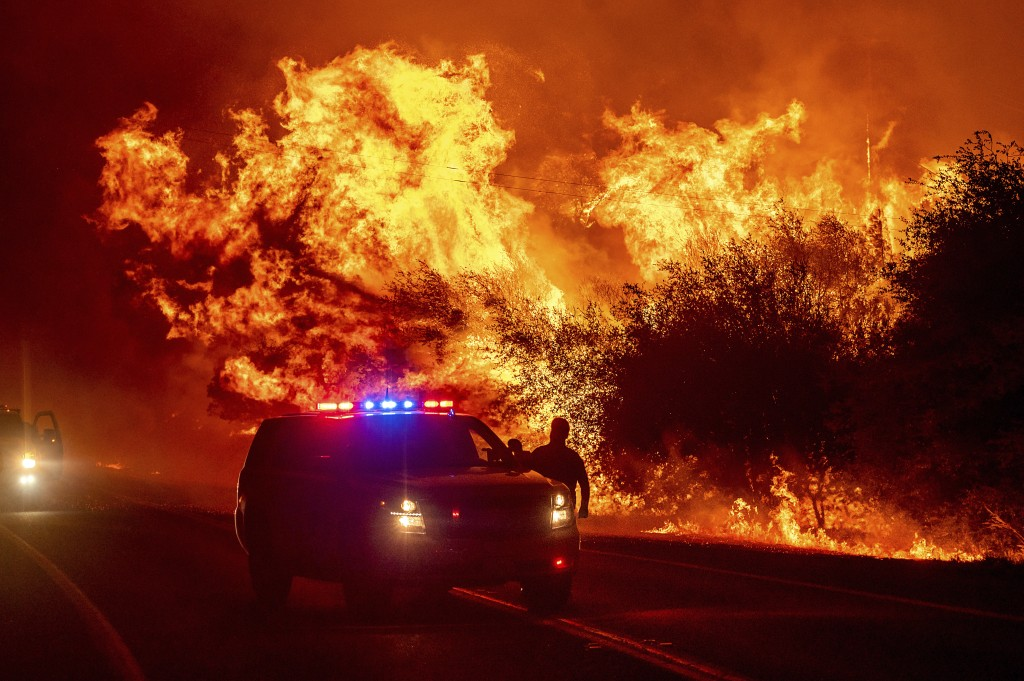 FILE - In this Sept. 9, 2020, file photo, flames lick above vehicles on Highway 162 as the Bear Fire burns in Oroville, Calif. The blaze, part of the ...