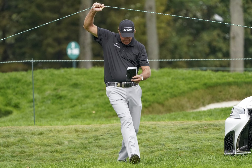 Phil Mickelson, of the United States, lifts a rope to cross over to the sixth tee during the first round of the US Open Golf Championship, Thursday, S...