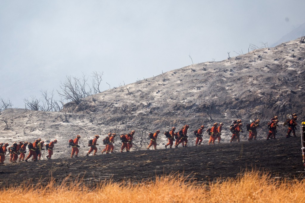 FILE - In this Sept. 5, 2020, file photo, members of a hand crew work on the fire line in Yucaipa, Calif.  Two unusual weather phenomena combined to c...