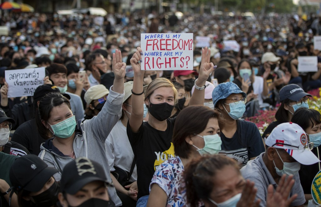 Pro-democracy activities display placards and raise a three-fingers salute, a symbol of resistance during a protest at Democracy Monument in Bangkok, ...