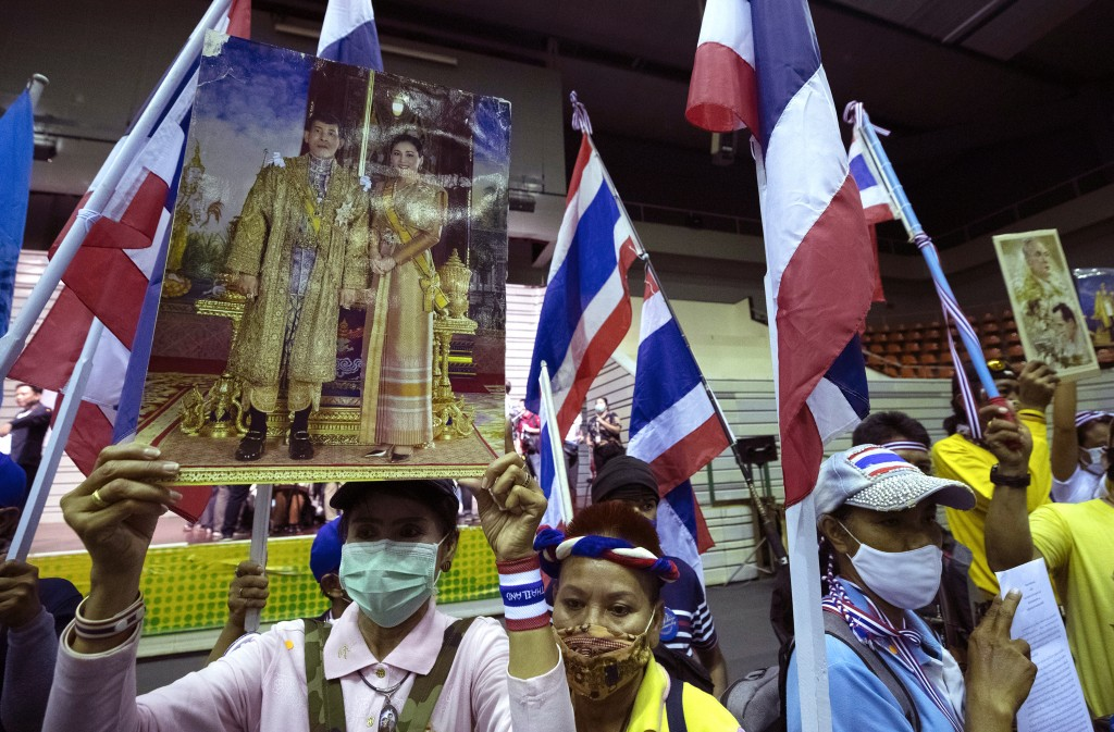Supporters of the Thai monarchy hold up images of King Maha Vajiralongkorn and Queen Suthida during a rally in Bangkok, Thailand, Sunday Aug. 30, 2020...