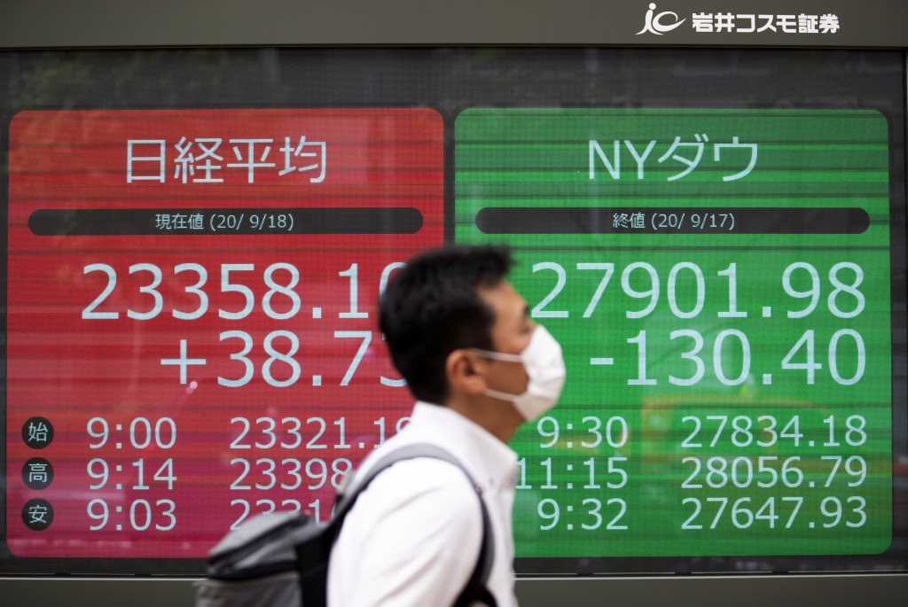 A man walks by screens showing Japan's Nikkei 225 index, left, and the Dow Jones Industrial Average, right, at a securities firm in Tokyo on Friday, S...