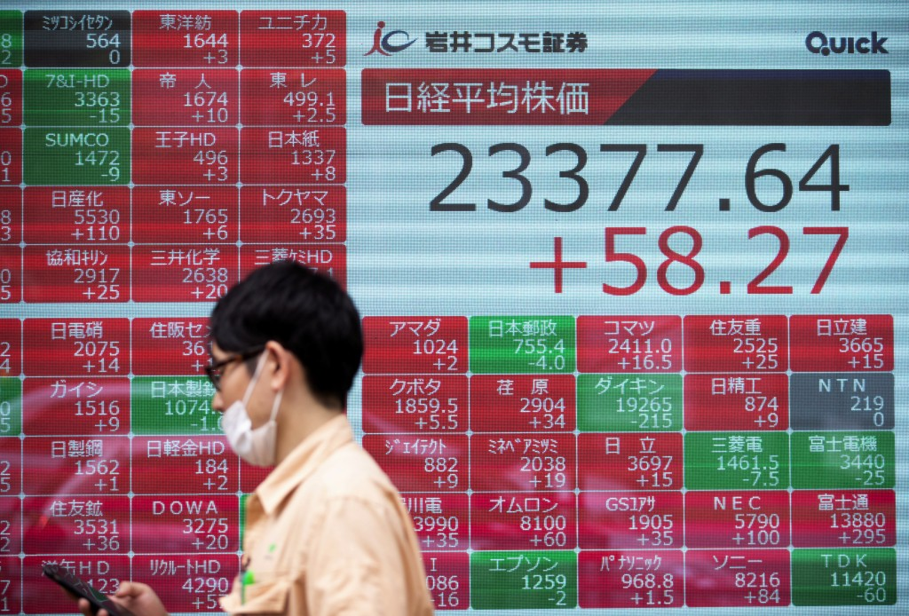 A man walks by screens showing Japan's Nikkei 225 index at a securities firm in Tokyo on Friday, Sept. 18, 2020. Asian shares were slightly higher Fri...