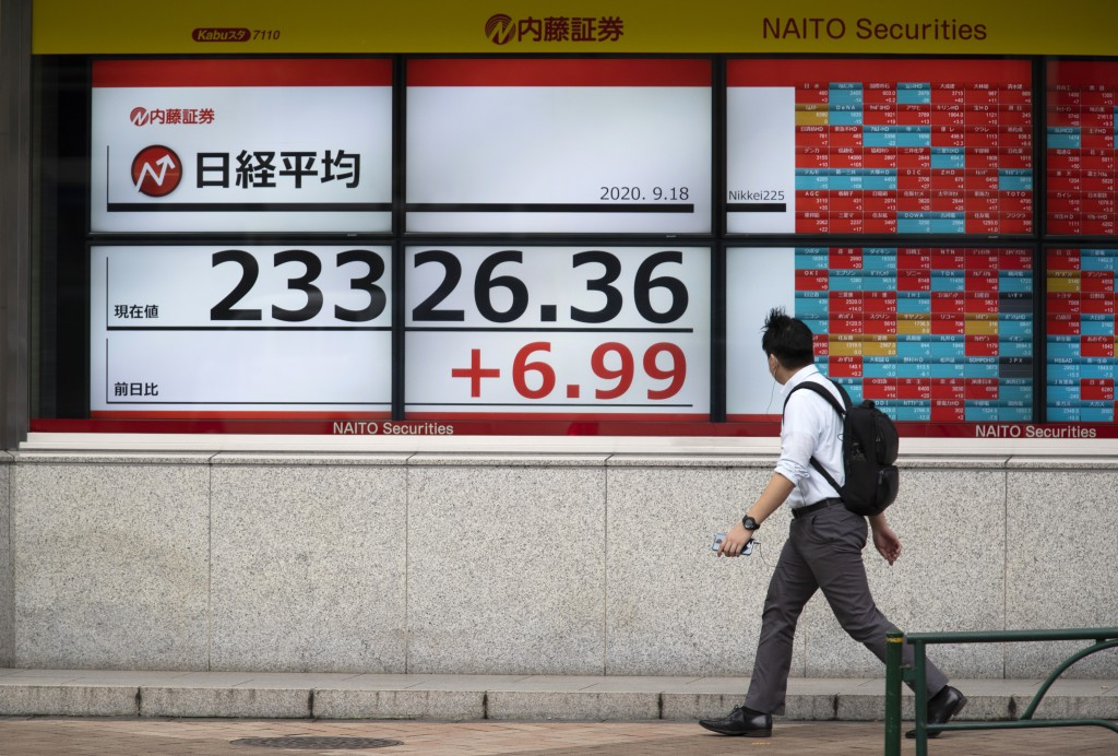 A man looks at screens showing Japan's Nikkei 225 index at a securities firm in Tokyo on Friday, Sept. 18, 2020. Asian shares were slightly higher Fri...