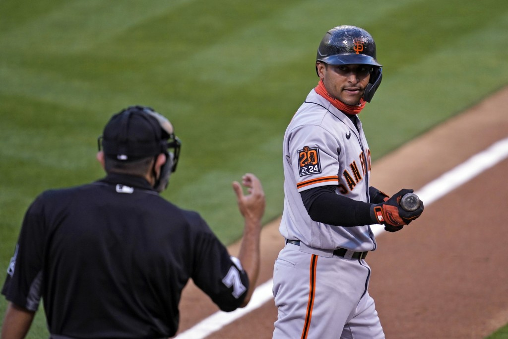 San Francisco Giants' Donovan Solano, right, looks at home plate umpire Alfonso Marquez and walks back to the dugout after striking out swinging again...