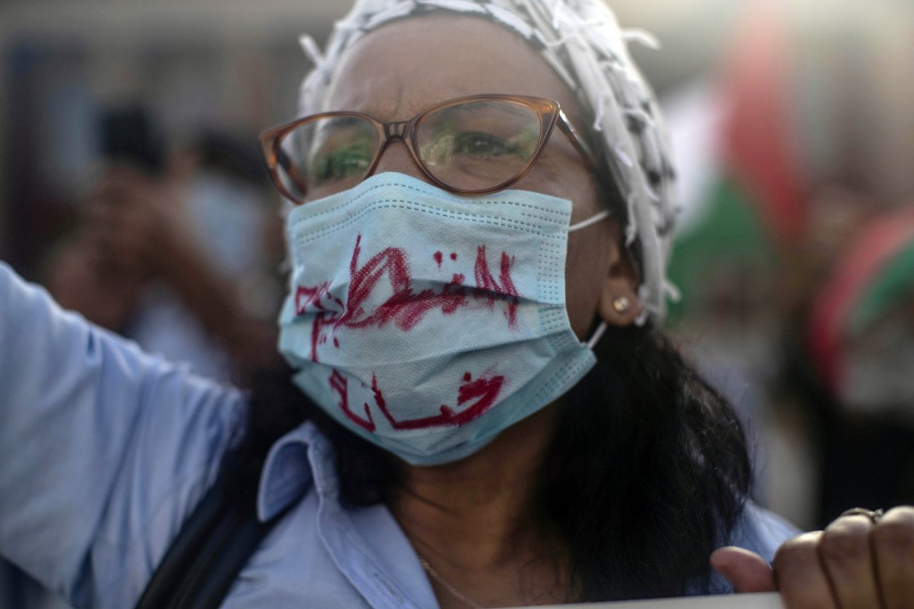 A woman wearing a face mask to prevent the spread of coronavirus chants slogans during a protest against normalizing relations with Israel, in Rabat, ...