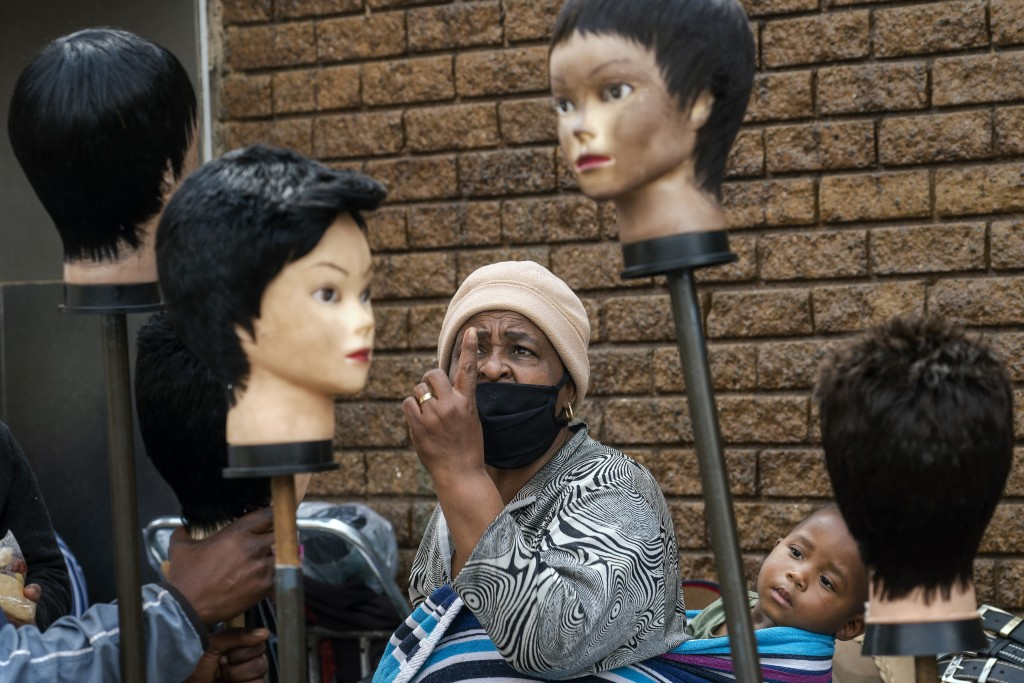 A woman carrying a child on her back looks at wigs on sale at the Baragwanath Taxi Rank in Soweto, South Africa, Wednesday, Sept. 16, 2020. The offici...