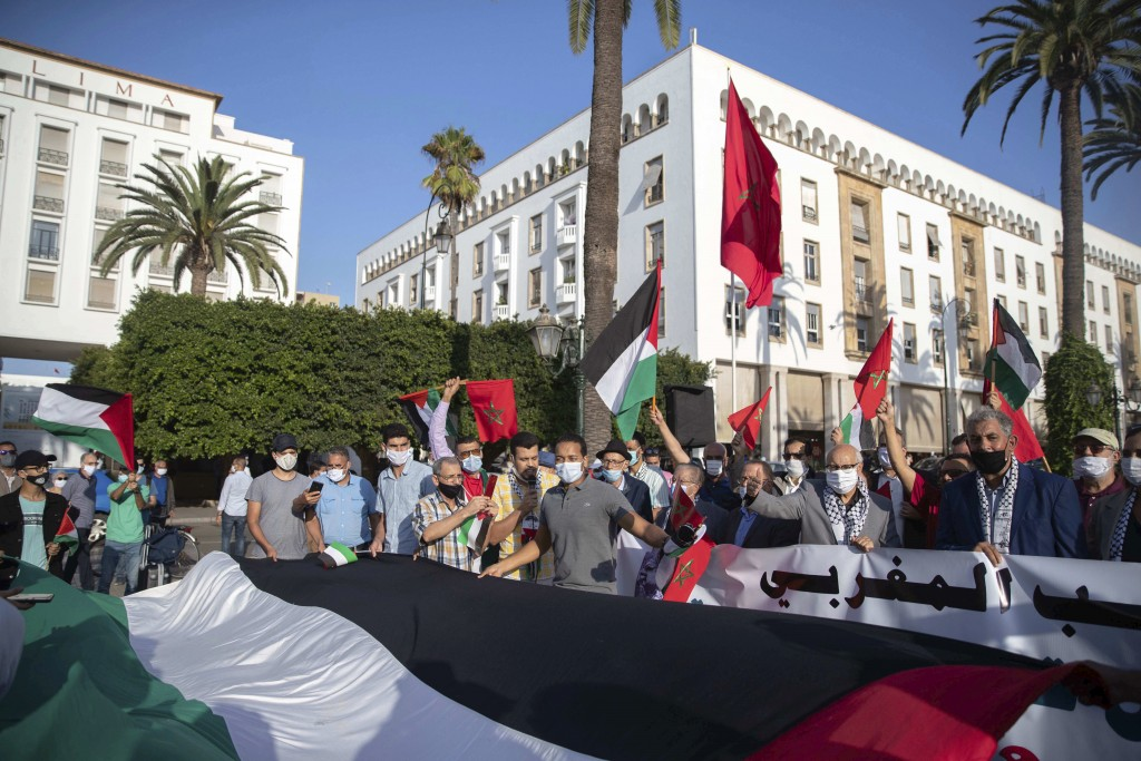 People hold a large Palestinian flag during a protest against normalizing relations with Israel, in Rabat, Morocco, Friday, Sept. 18, 2020. Despite a ...