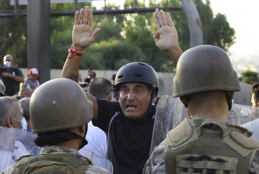 An anti-government protester reacts in front of Lebanese soldiers during a protest against President Michel Aoun near the presidential palace in Baabd...