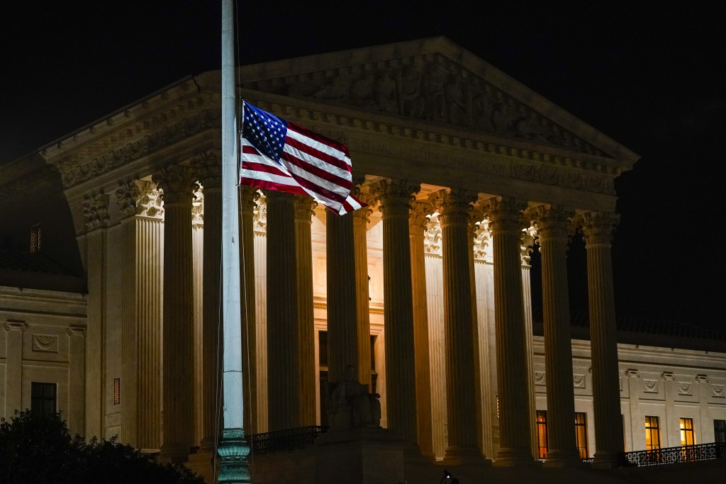 The American flag blows in the wind after it was lowered to half-staff Friday, Sept. 18, 2020, in Washington, after the Supreme Court announced that S...